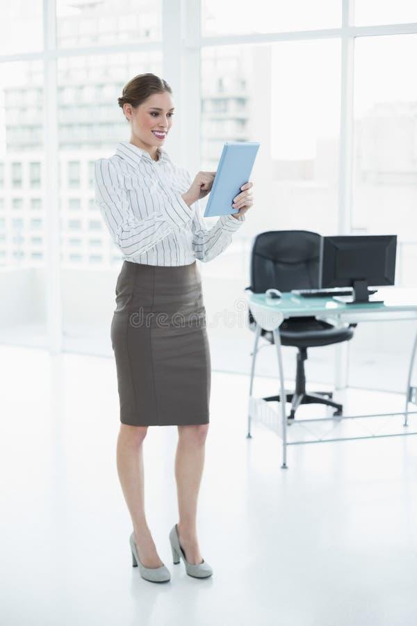 Donna di affari elegante felice che per mezzo della sua compressa immagine stock libera da diritti