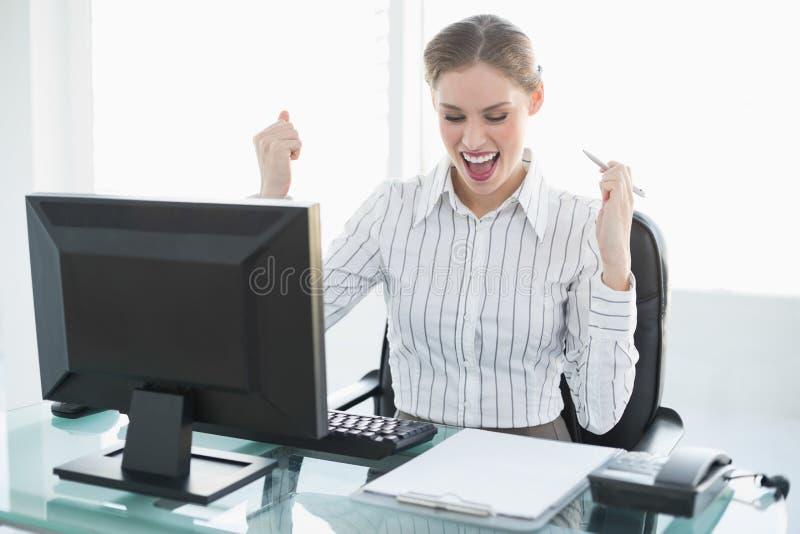 Donna di affari elegante felice che si siede al suo scrittorio davanti al suo computer fotografia stock