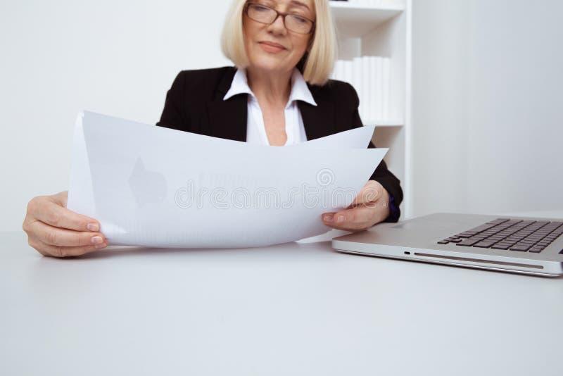 Donna di affari elegante nel funzionamento di vetro nell'ufficio bianco con carta fotografie stock