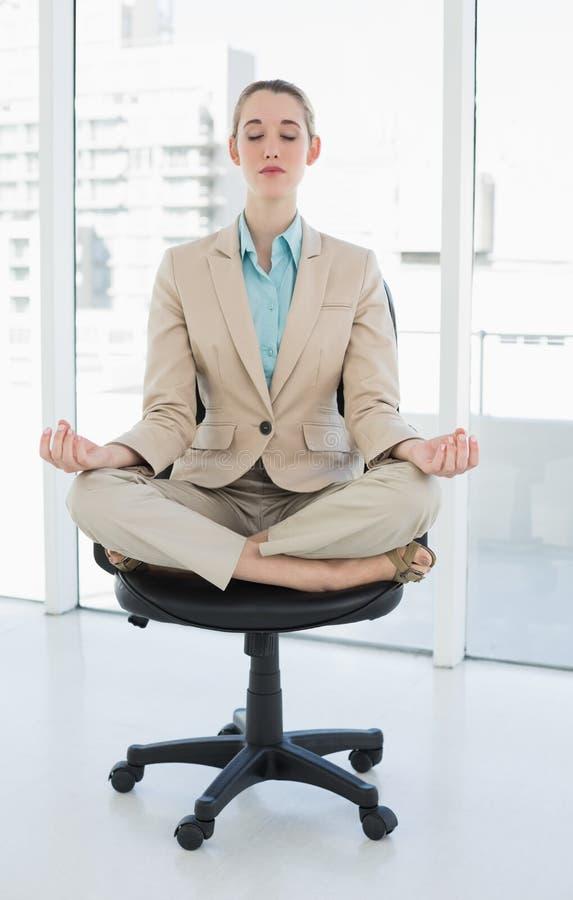 Donna di affari elegante pacifica che si siede nella posizione di loto su poltrona girevole immagine stock