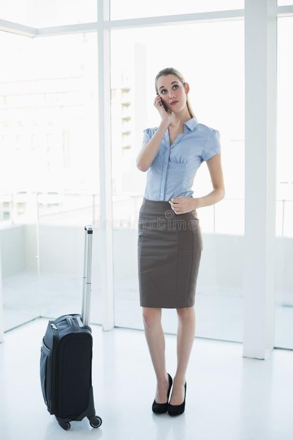 Donna di affari elegante premurosa che telefona mentre stando nell'ufficio immagine stock