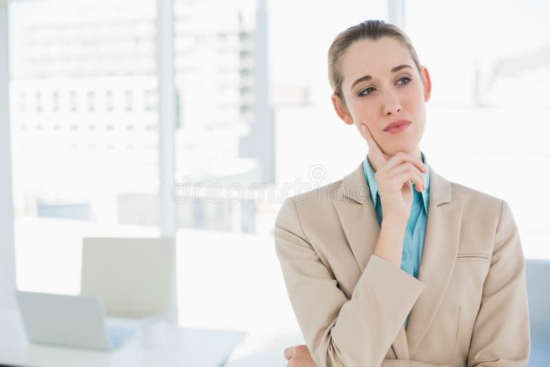 Donna di affari elegante premurosa sveglia che sta nel suo ufficio fotografia stock