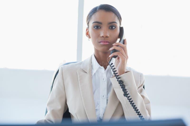 Donna di affari elegante severa sul telefono fotografie stock