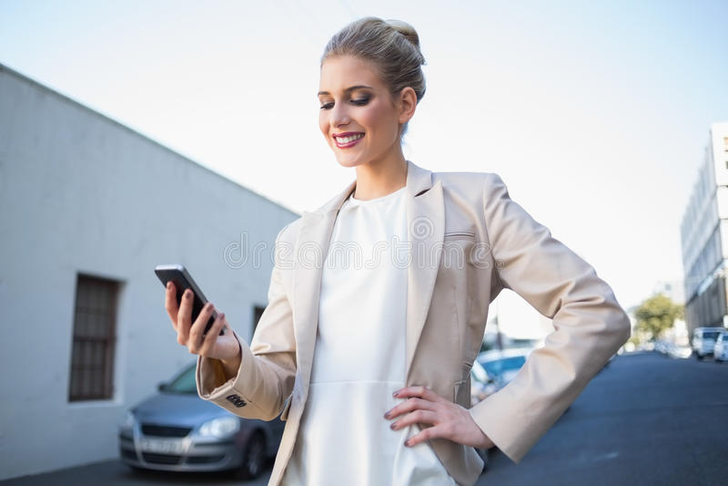 Donna di affari elegante sorridente che esamina il suo smartphone fotografia stock
