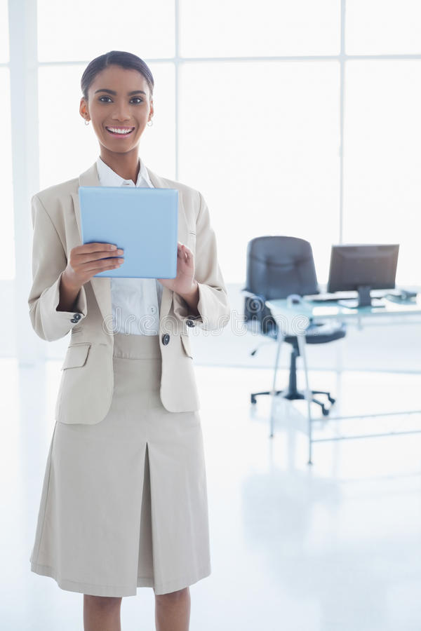 Donna di affari elegante sorridente che per mezzo della sua compressa fotografia stock libera da diritti