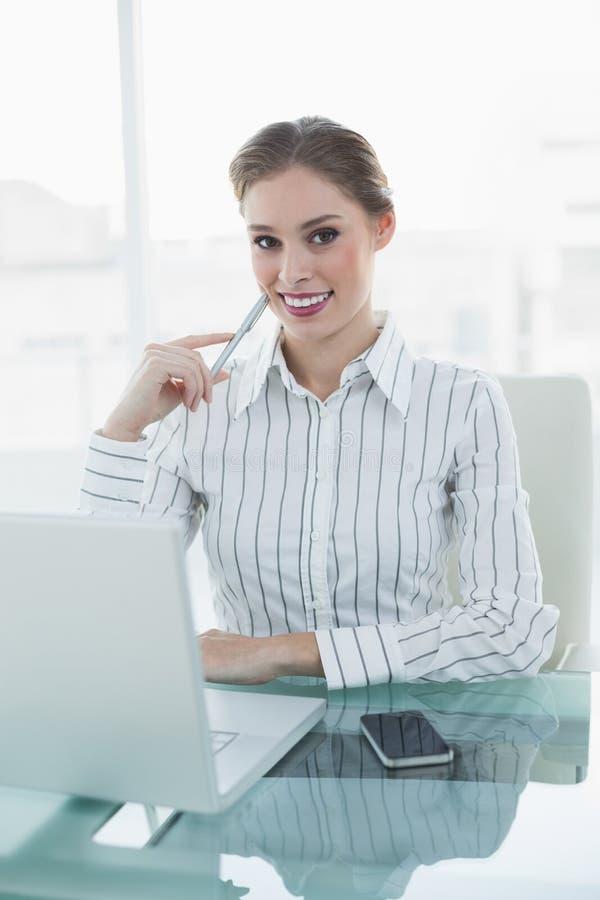 Donna di affari elegante sorridente che si siede al suo scrittorio davanti al computer portatile ed allo smartphone fotografia stock