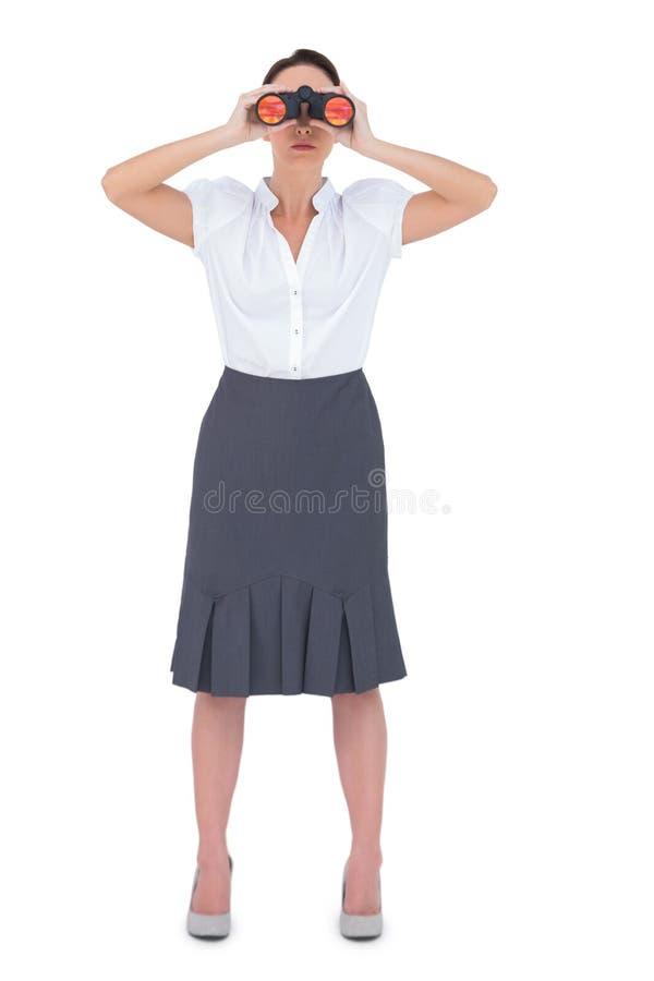 Donna di affari elegante Unsmiling che guarda tramite il binocolo fotografia stock libera da diritti