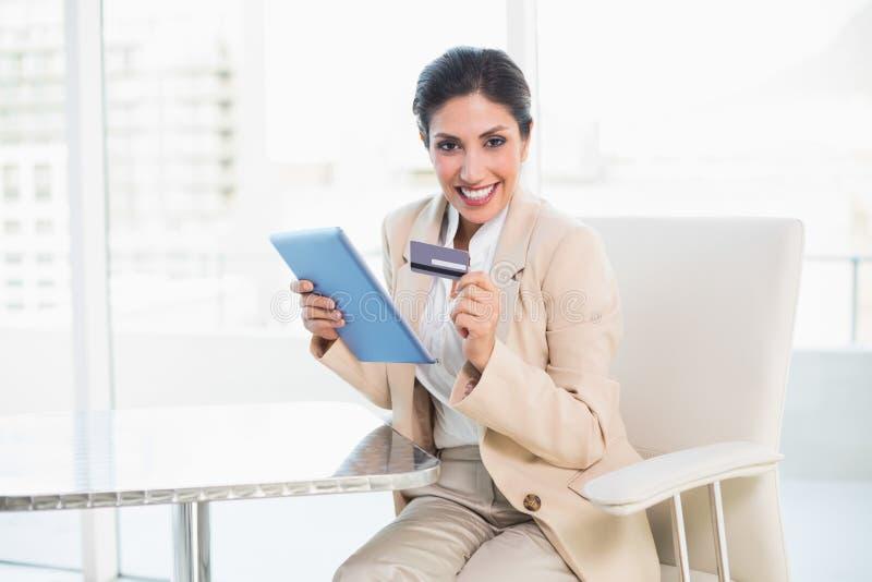 Donna di affari emozionante che compera online con il pc della compressa immagini stock