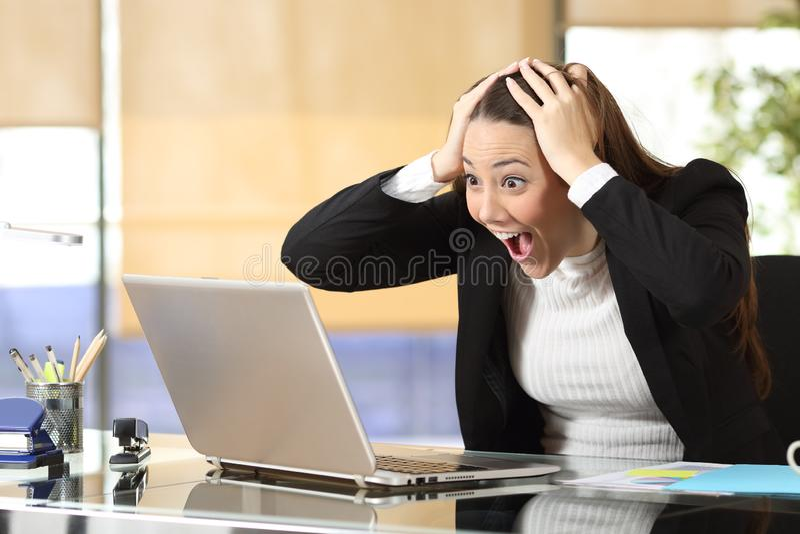 Donna di affari emozionante che controlla il contenuto online del computer portatile fotografia stock