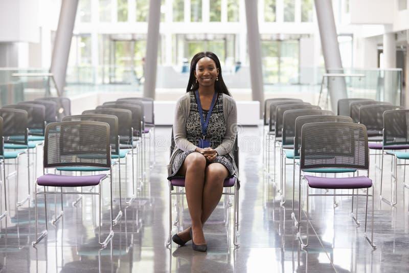 Donna di affari In Empty Auditorium che prepara fare discorso fotografie stock