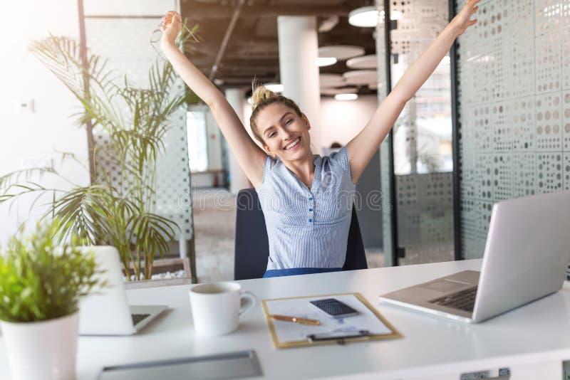 Donna di affari entusiasta con le armi alzate in ufficio immagini stock