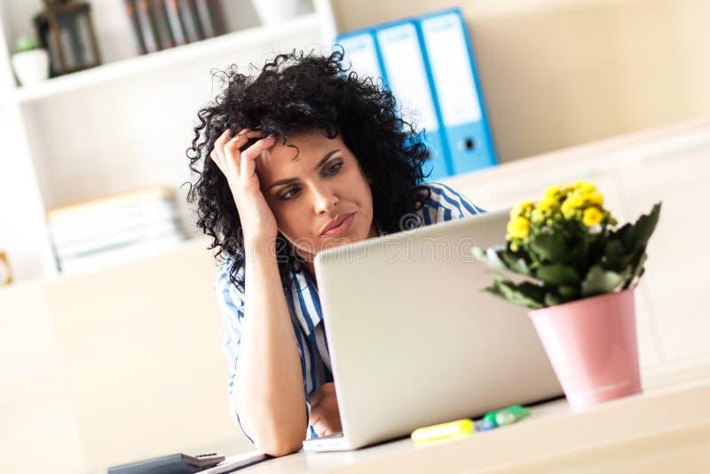 Donna di affari esaurita che esamina computer portatile fotografia stock