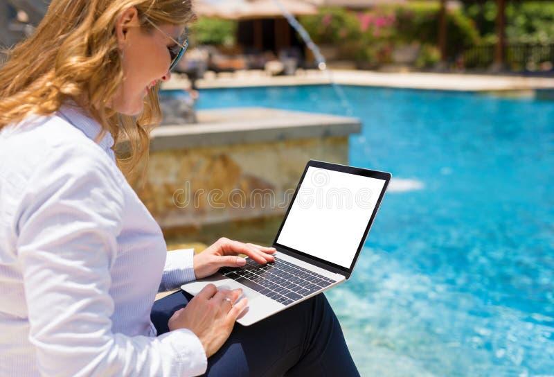 Donna di affari facendo uso del computer portatile sulla vacanza nella località di soggiorno dallo stagno fotografie stock