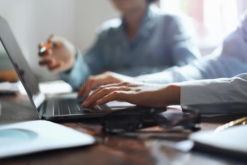 donna di affari facendo uso della mano del computer portatile che scrive sulla tastiera per la riunione del gruppo in ufficio Con fotografie stock libere da diritti
