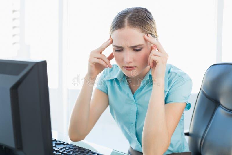 Donna di affari facente smorfie di classe che ha un'emicrania immagine stock
