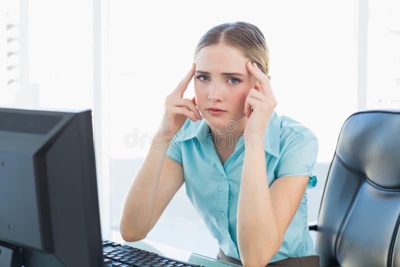 Donna di affari facente smorfie di classe che soffre un'emicrania fotografie stock libere da diritti