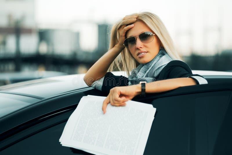 Donna di affari faticosa con un'automobile immagine stock