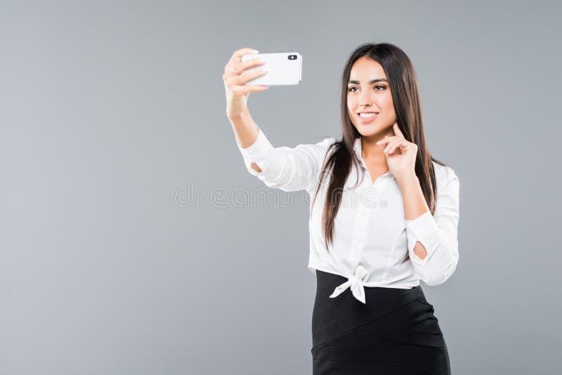 Donna di affari felice che fa la foto del selfie sullo smartphone o che fa video chiamata sopra fondo bianco fotografie stock libere da diritti