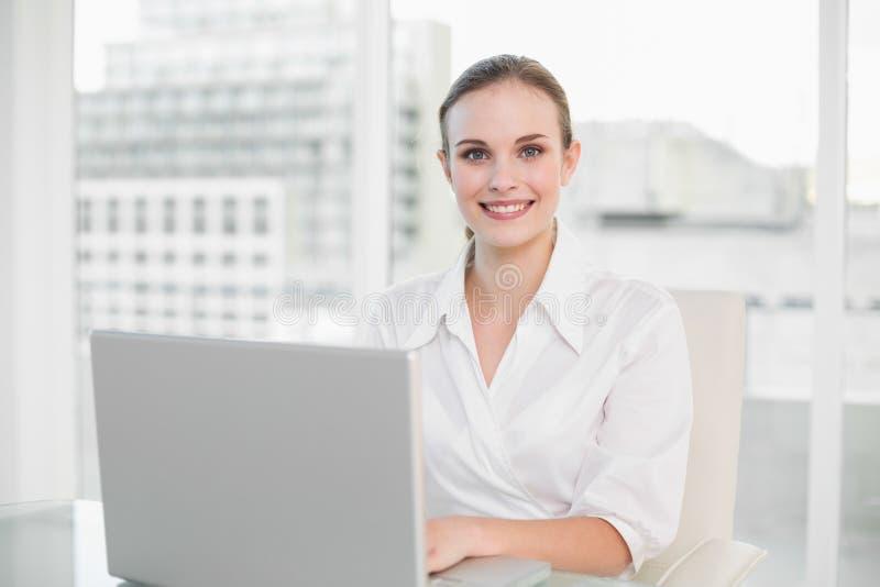 Donna di affari felice che per mezzo del computer portatile che esamina macchina fotografica fotografia stock