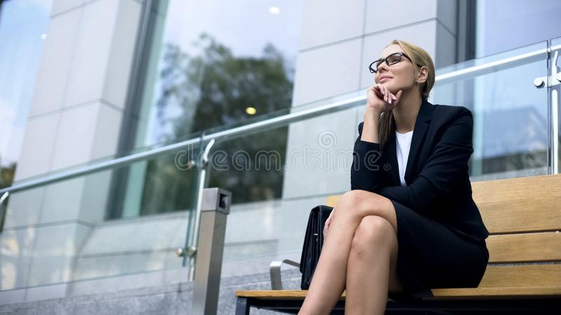 Donna di affari felice che si siede sul banco e che sorride, accogliendo nuovo giorno, lavoro favorito immagine stock libera da diritti
