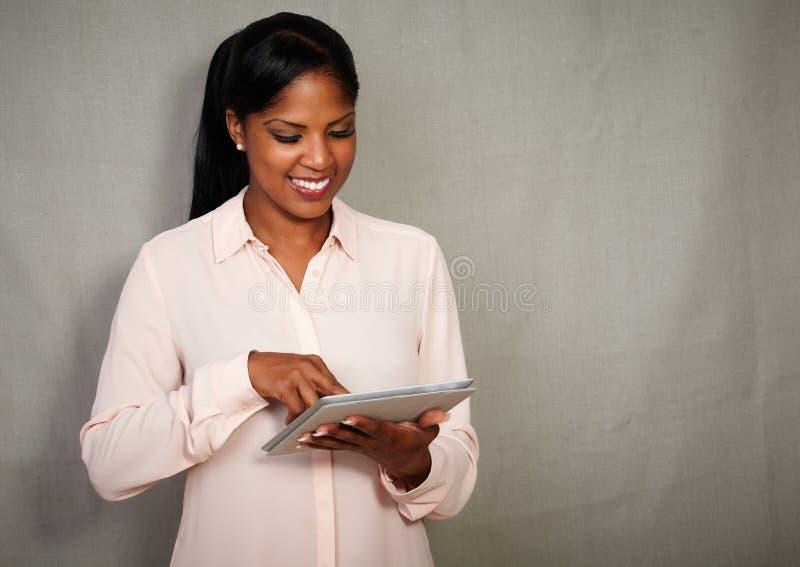 Donna di affari felice che sorride mentre per mezzo di una compressa immagini stock