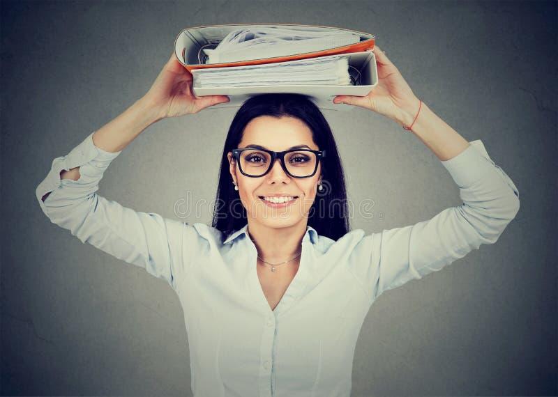 Donna di affari felice con i raccoglitori dell'ufficio che stanno ghignanti alla macchina fotografica fotografia stock