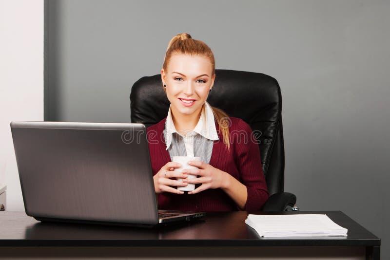 Donna di affari felice con la tazza all'ufficio fotografie stock
