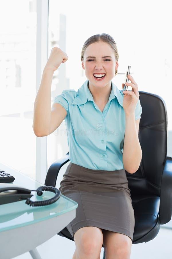 Donna di affari felice di classe sul telefono che incoraggia con le armi alzate fotografia stock libera da diritti