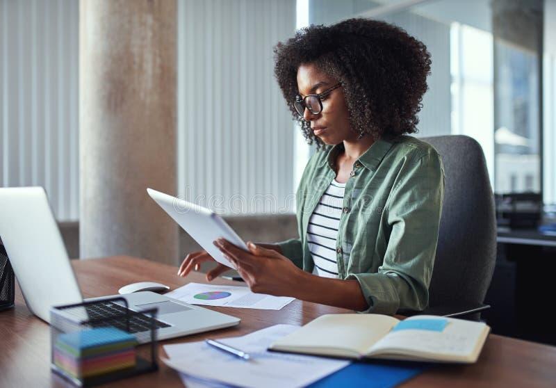 Donna di affari femminile che analizza la relazione di attività nell'ufficio fotografia stock
