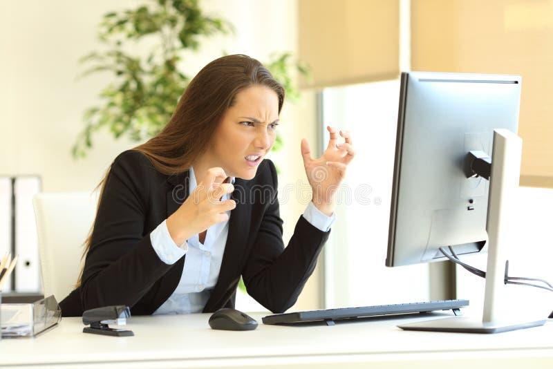 Donna di affari furiosa che per mezzo di un computer immagini stock
