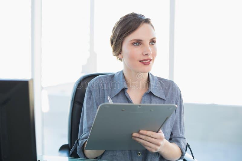 Donna di affari giovane di pensiero che tiene una lavagna per appunti mentre sedendosi al suo scrittorio immagini stock