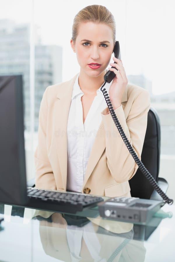 Donna di affari graziosa aggrottante le sopracciglia che risponde al telefono fotografia stock