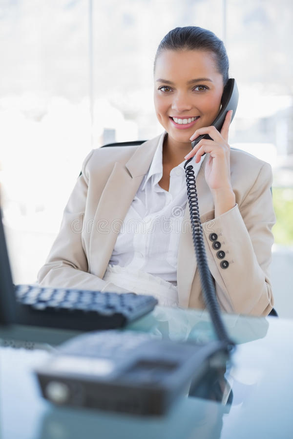 Donna di affari graziosa allegra che risponde al telefono immagine stock