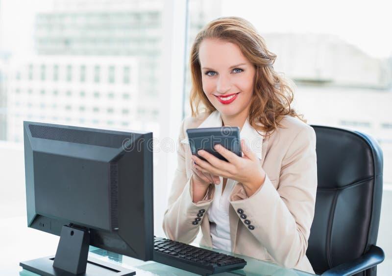 Donna di affari graziosa calma che per mezzo di un calcolatore fotografie stock libere da diritti
