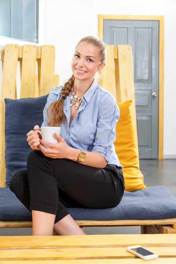Donna di affari graziosa che beve il caffè caldo di mattina e che sogna nel sottotetto moderno Donna in businness Free lance dent immagini stock