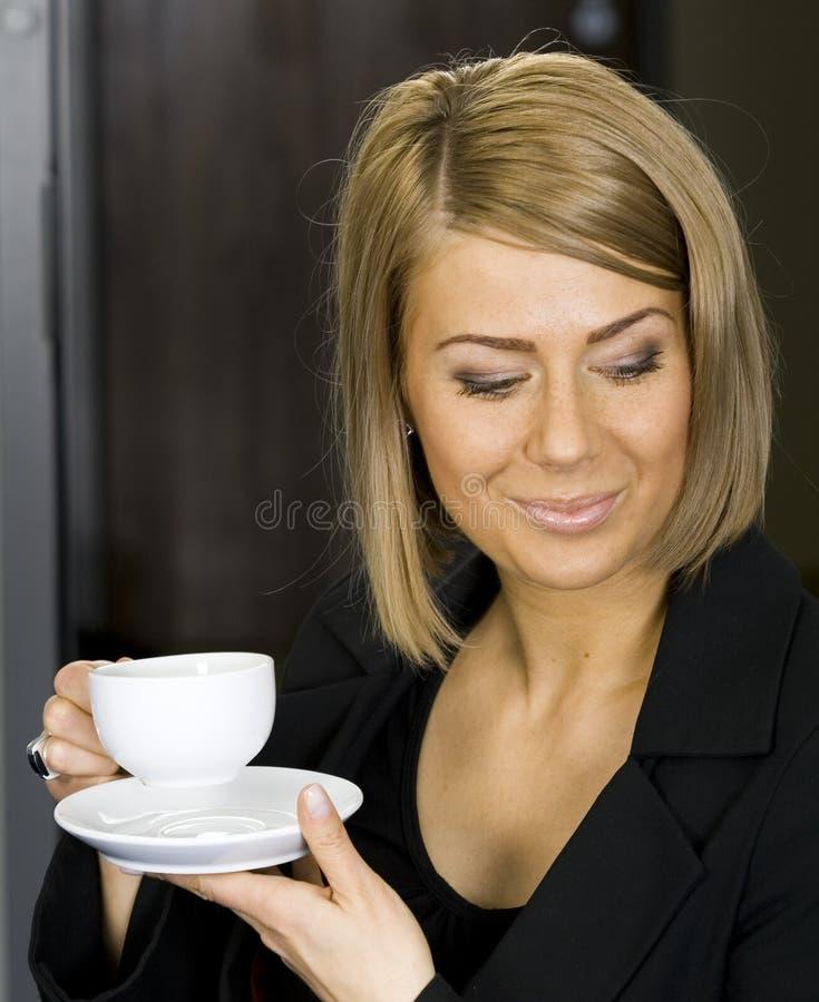 Donna di affari graziosa che mangia il suo caffè di mattina fotografia stock libera da diritti