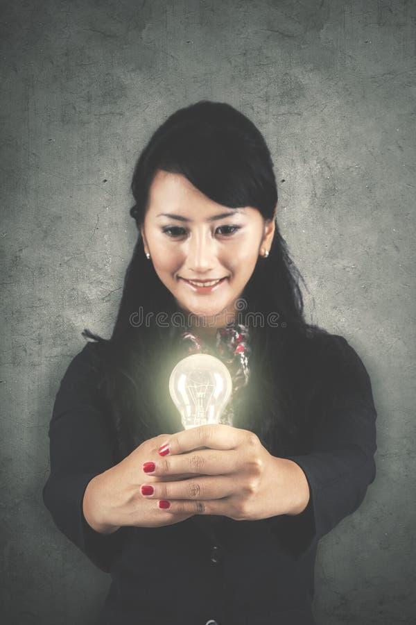 Donna di affari graziosa che mostra una lampadina luminosa immagini stock