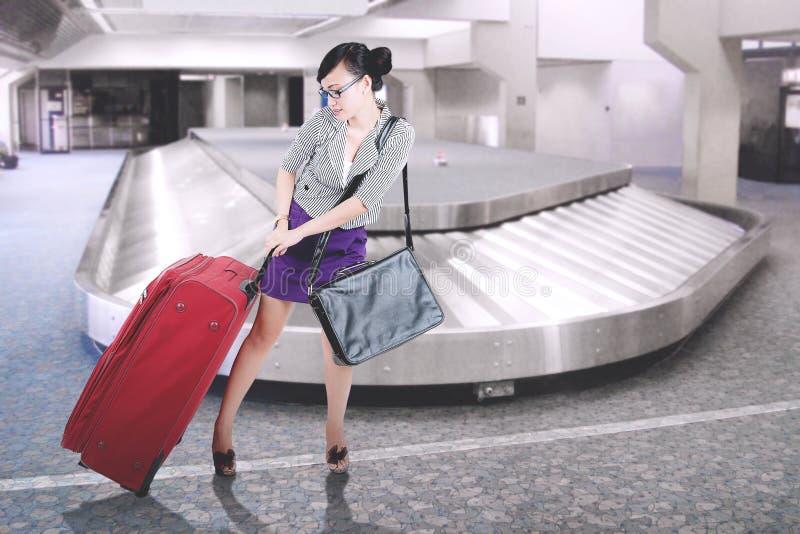 Donna di affari graziosa che porta una valigia all'aeroporto immagini stock libere da diritti
