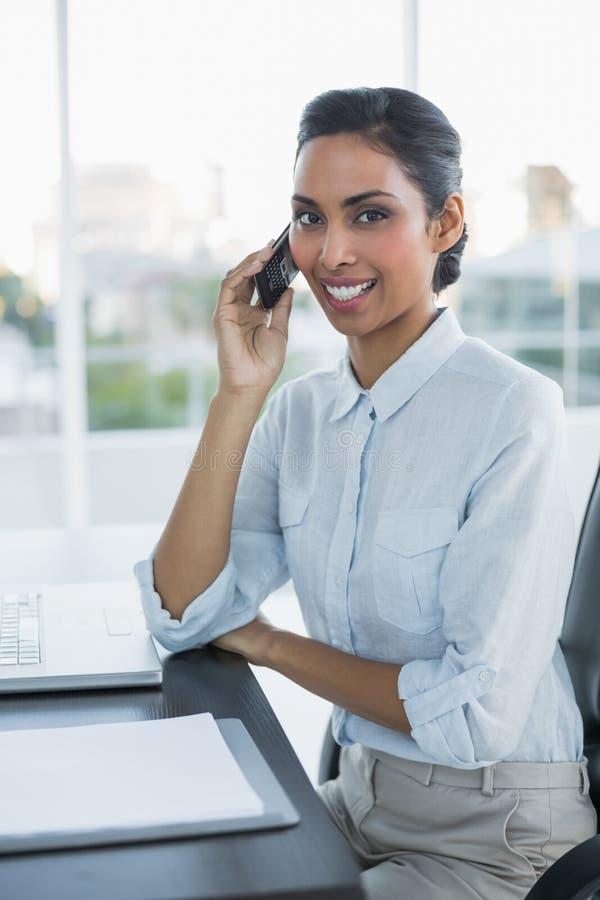 Donna di affari graziosa che telefona con lo smartphone che sorride alla macchina fotografica fotografie stock
