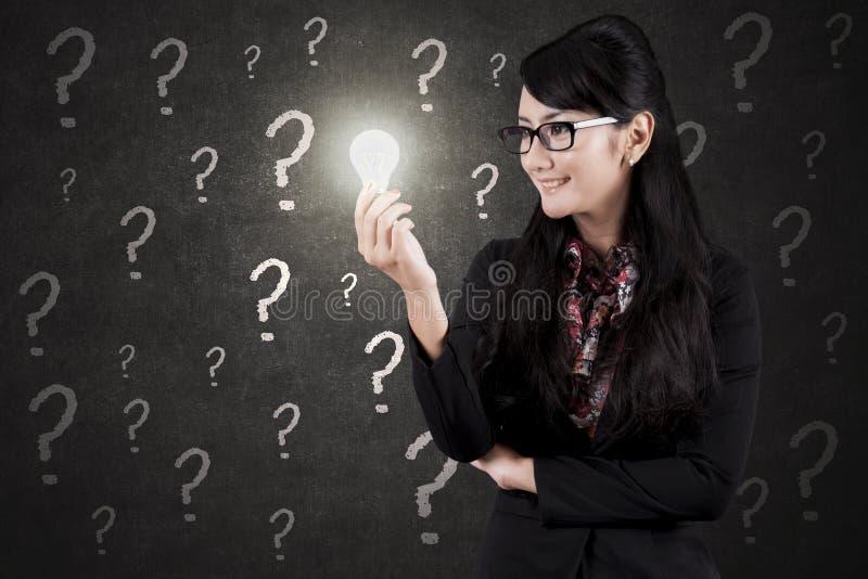 Donna di affari graziosa con la lampadina ed i punti interrogativi immagine stock
