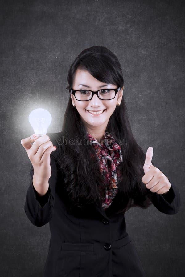 Donna di affari graziosa con la lampadina luminosa fotografia stock