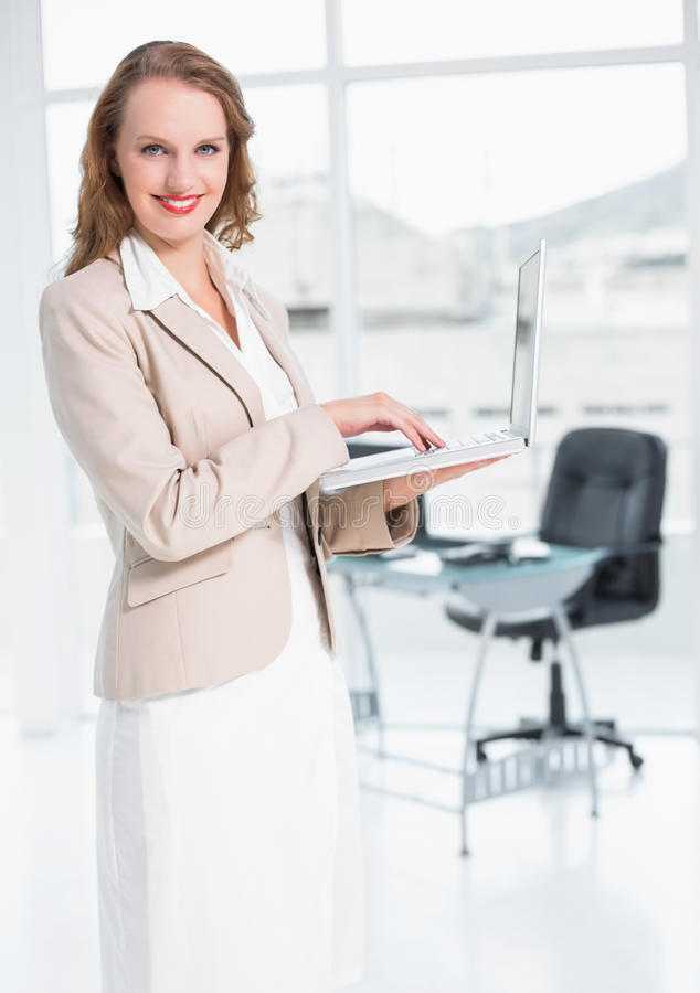 Donna di affari graziosa contenta che per mezzo del computer portatile immagini stock