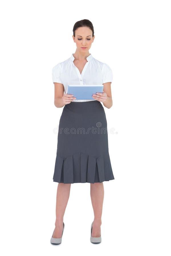 Donna di affari graziosa messa a fuoco che per mezzo del computer della compressa immagini stock