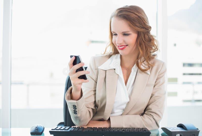 Donna di affari graziosa piacevole che esamina il suo telefono cellulare immagini stock