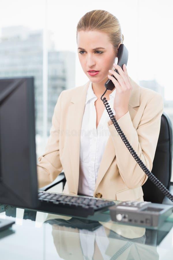 Donna di affari graziosa seria che risponde al telefono fotografia stock libera da diritti