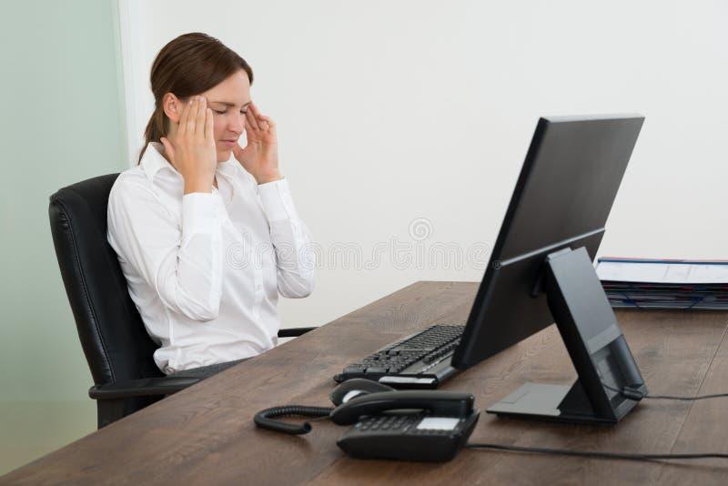 Donna di affari Having Head Pain in ufficio immagini stock libere da diritti