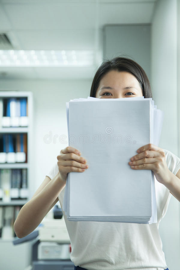 Donna di affari Hiding Behind Paper immagine stock libera da diritti