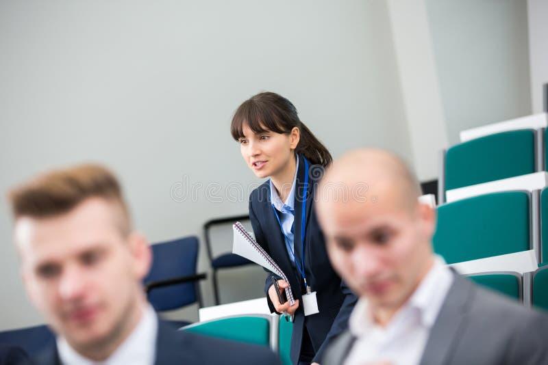 Donna di affari Holding Book While che sta nella conferenza corridoio immagini stock