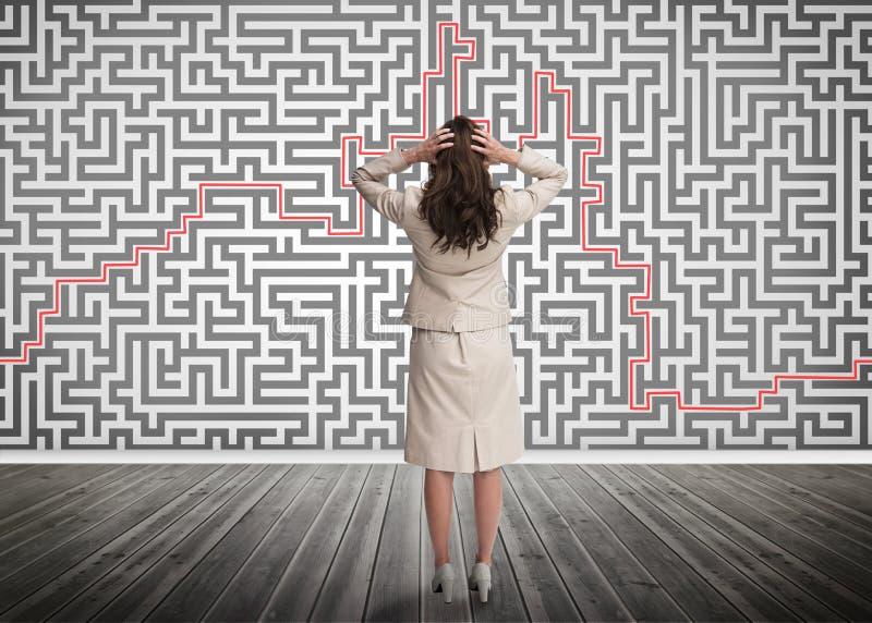 Donna di affari imbarazzata che esamina un labirinto immagini stock libere da diritti