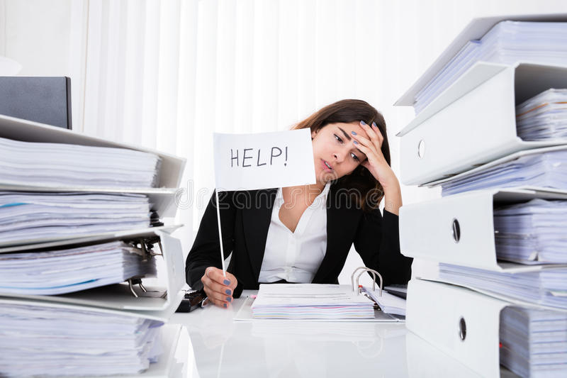 Donna di affari infelice Holding Help Flag in ufficio immagine stock libera da diritti